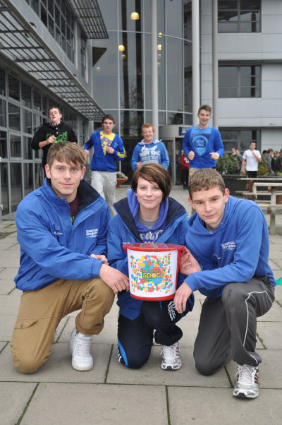 Students with the Children in Need collection bucket. In the background, the students can be seen in action running the marathon. Front Left-Right: Dave Cleaton, Danielle Hughes, Tom Lawrenson