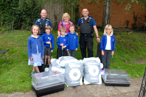 Police Community Support Officers Neil Darley and Ivan Columbell, who delivered the compost to the school, are pictured with headteacher Mrs Geraldine Dunkerley and pupils Rebecca Edge, Ollie Hodgson, Jimmy Meredith, Harry Wagner and Tessa Delafield.