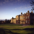 Sunlight and shadows bathe the East Front of Dudmaston Hall as the evening sun sets.