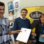 College student Liam Evans gives his completed CV to Julie Preece of Ludlow Food Centre with Jobs Fair organiser Philip Dunne MP looking on.