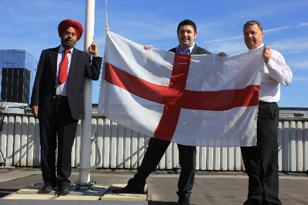 Council leader Kuldip Sahota, Councillor Shaun Davies and Councillor Richard Overton flying the England flag from Addenbrooke House.