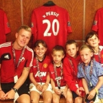 Connor Courtney, a coach with Crossbar Coaching Education in Sport, and some local youngsters in the Manchester United dressing room on a previous visit to Old Trafford.