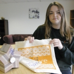 Corrie Ellis, online sales and marketing co-ordinator, with the signed Tinie Tempah items