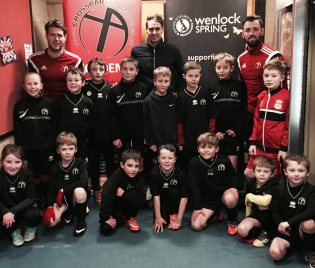 Wolves midfielder Dave Edwards, centre of the back row, lines up with Crossbar Coaching Education in Sport coaches Kevin Sandwith, left, and Jamie Haynes and a host of local youngsters at the Crossbar Academy