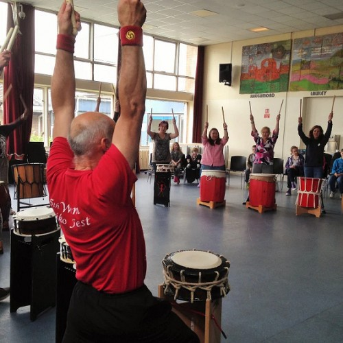 Parents and children try out Taiko drums at summer school