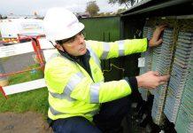 A BT Openreach engineer working at a fibre broadband cabinet