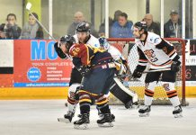 Rick Plant and Sam Oakford keep an eye on the puck against Guildford Flames on Wednesday night. Photo: Steve Brodie