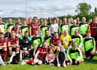 The two teams and younger family members lined up together at the end of the charity match
