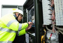 An Openreach engineer works on a roadside fibre broadband cabinet to connect another household to the faster technology