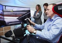 Pictured trying out the Formula 1 simulator is Philip Boot of Kloeckner Metals UK, watched by Sophie Norton (left) and Amy Nock of Pure Telecom
