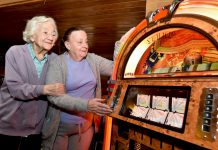 Enid Verdmore and Margaret Richardson enjoy listening to a jukebox at Innage Grange