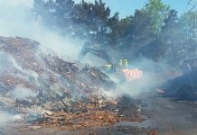 Firefighters worked in rotas to contain the fire which involved a mound of wood and chippings, and two machines