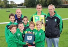Nova United chairman, Ted Bowen (extreme right), with players, coaches and the new defibrillator and it's mounting case
