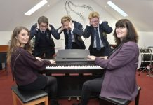 From left, pupils Daniel Cubbon, Jonty Watt and James Sale, listening to Sonya Bagley try out the school's current piano with parent fundraiser Caroline Haves