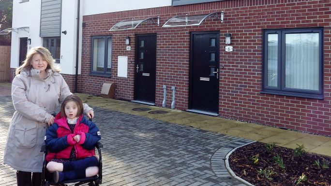 Ava is pictured with her mum Emma outside their new home in Oswestry