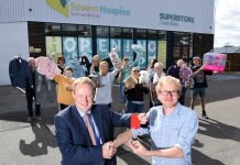 Paterson Enterprises director Edward Goddard (left) hands over the key to the new superstore to Ross Henderson, Severn Hospice's head of retail, watched by staff
