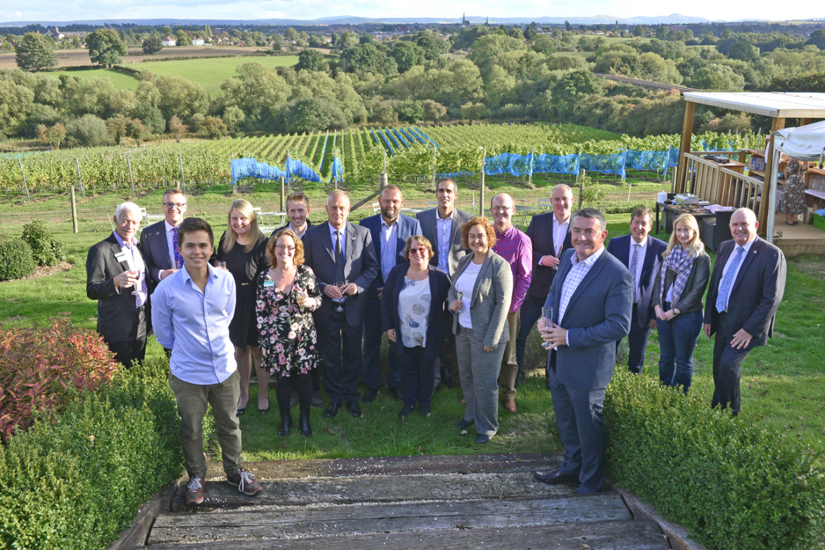 Mark Stevens (left) and Nick Jones (right) with chamber patrons and guests above the vine covered slopes of Hencote Estate
