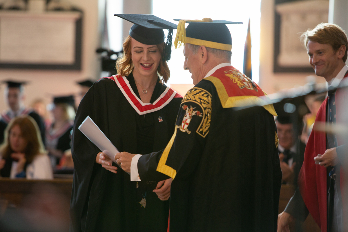 Dr Gyles Brandreth presents a UCS student with their degree certificate