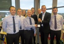 Stephen Higgins receives a bottle of champagne and a cheque from Salop Leisure's chairman Tony Bywater to mark his 25 years' service watched by the company's accounts team