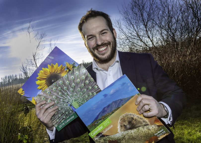 Edward Thomas, Group Head of Marketing and Communications for the Trust with calendars from previous years