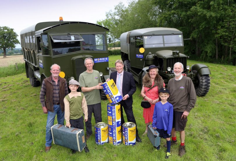 Morris Lubricants' chairman Andrew Goddard presents drums of oil to Ben Kaye watched by his sons, Sam and Will, his parents Tom and Julie Kaye and Robin Frostick with the Scammell Pioneer R100 and AEC Matador in the background