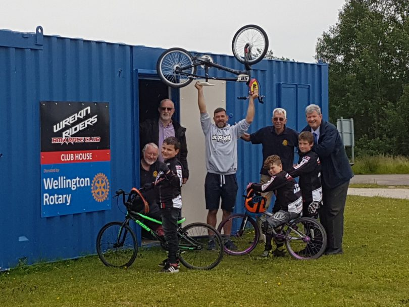 Club chairman and coach Kieran Edwards celebrates the official hand over of the new clubhouse with young riders and Rotary Club of Wellington members which kindly donated the clubhouse