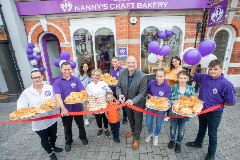Cllr Lee Carter cuts the ribbon at the opening of Nanny's Craft Bakery in Wellington with the Dimitrov family