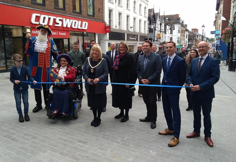 Councillor Ann Hartley, Chairman of Shropshire Council, cuts the ribbon at the top of Pride Hill, watched by Martin Wood, town crier, and representatives from Shropshire Council, Shrewsbury Town Council, Shrewsbury BID and McPhillips. Photo: Shropshire Council
