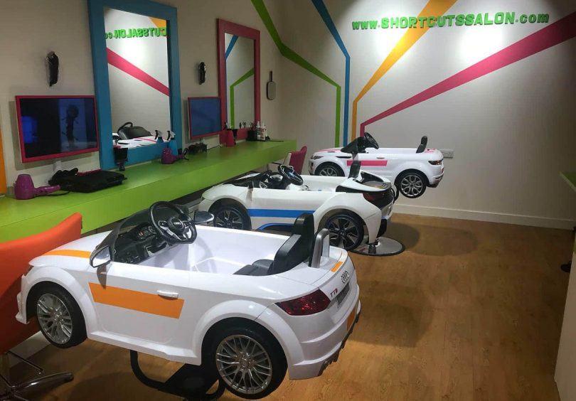 Young children can sit in a novelty car salon chair whilst having their hair cut
