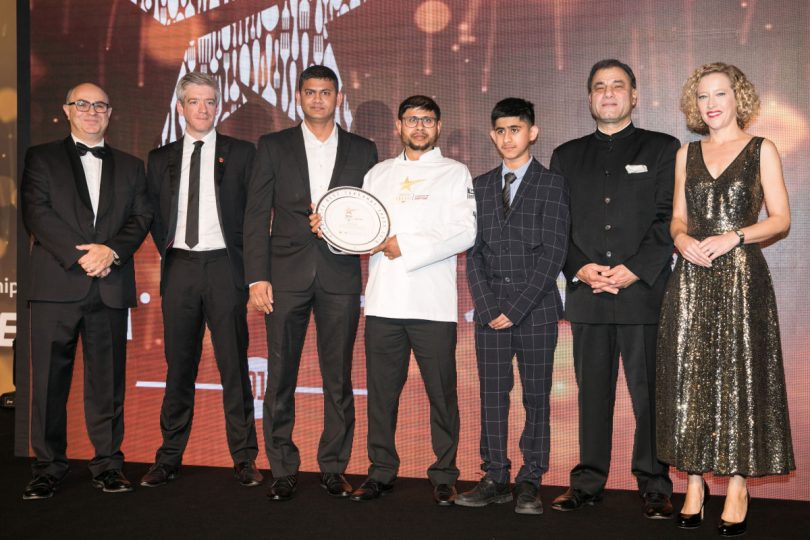 Pictured at the Curry Life Awards 2019 are Mr Adam Shaw, Journalist Broadcaster, Matt Bushby, The UK Director of Marketing for Just Eat, Mr Zillur Rohman, Taj Uddin, Mahim Uddin, Lord Karan Bilimoria, founder of Cobra Beer and Cathy Newman, Journalist and Broadcaster