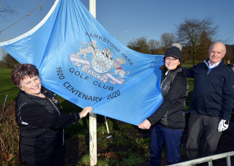 President Dale Benbow prepares to raise the club's centenary flag with Captains Christine and Stuart Apperley