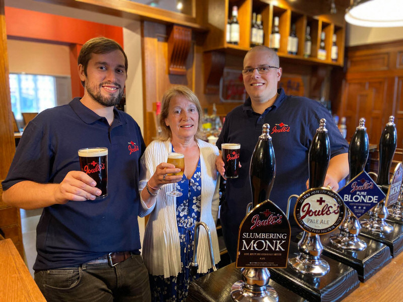 Pictured behind the bar are Alex Marsh, Landlord at the Swan with Heather and Rich Marsh