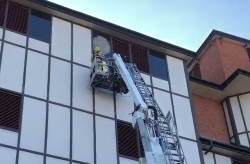 A firefighter works to remove the broken glass panel. Image: Craig Jackson / @SFRS_cjackson