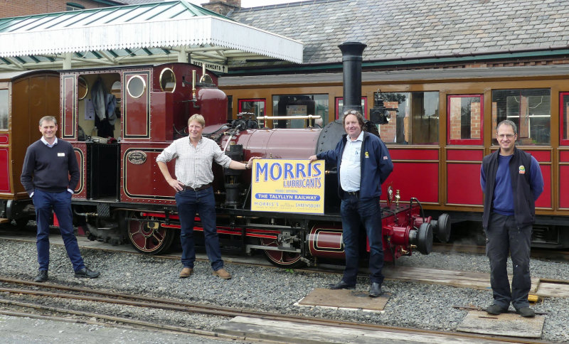Morris Lubricants' executive chairman Andrew Goddard (second form left) and the company's heritage account manager Keiron Thorogood hold one of the new signs watched by Talyllyn Railway's general manager Stuart Williams (left) and engineering manager Chris Smith (right)