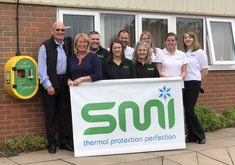The SMI team with the defibrillator outside their headquarters, on the Stafford Park industrial estate in Telford