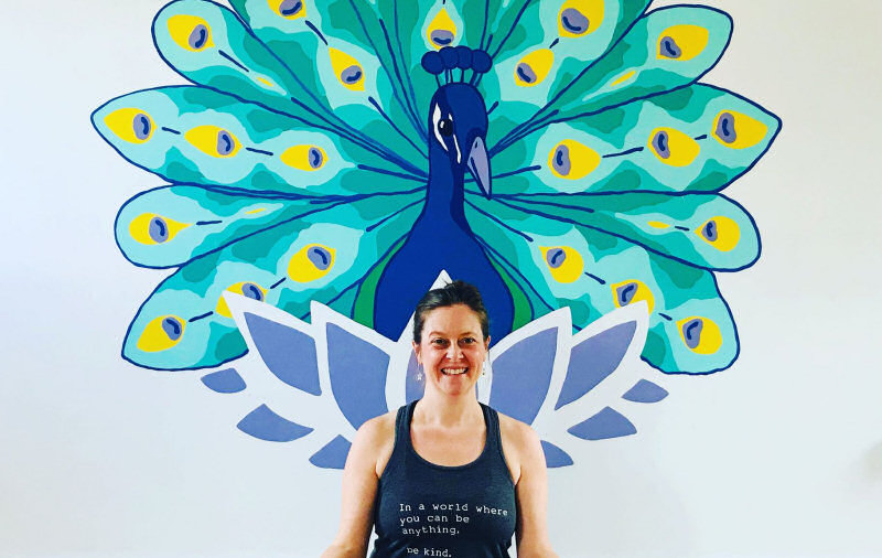 Jenna Blair with Matt Sewell's mural, which marks National Yoga Month this September